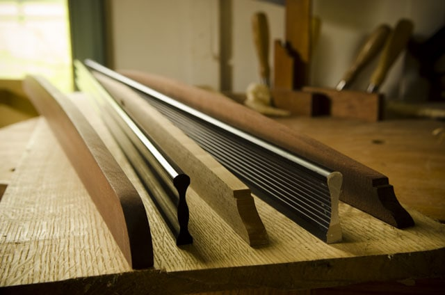 wooden and metal straight edges sitting on a roubo woodworking workbench