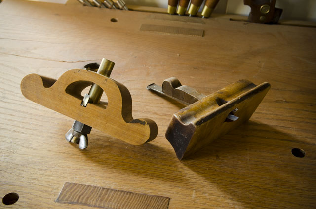 a wooden router plane with a thumb screw and another with a wedge