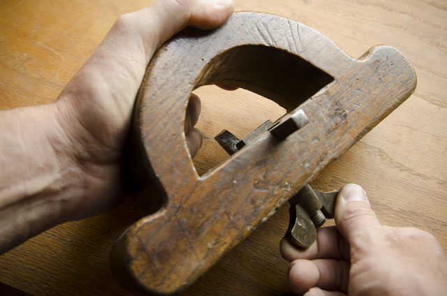 fingers tightening the thumb screw of a  wooden router plane
