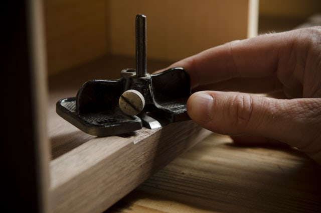 woodworker using a small router plane for hinge mortise