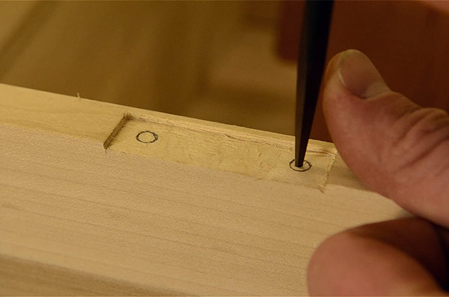 Using an awl to mark for a drilling whole while installing butt hinges on a dovetail chest