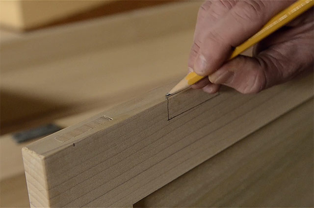 marking a mortise with a pencil while Installing butt hinges on the lid of a dovetail chest
