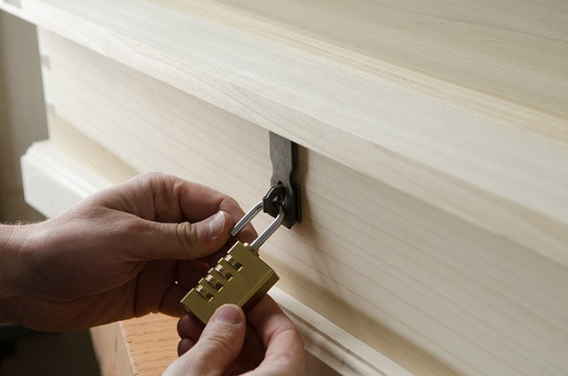 A Woodworker Locking A Brass Combination Padlock On A Padlock Hasp And Staple On A Wooden Dovetail Chest Box
